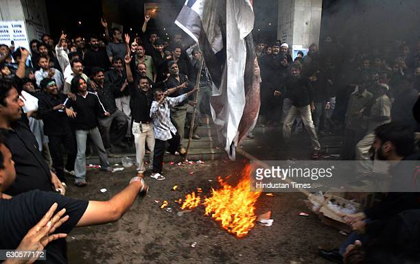 Demonstrations - Indian Shiite Muslims burn poster of US President George W Bush during a protest against the bombing of the major Shiite Askariya...