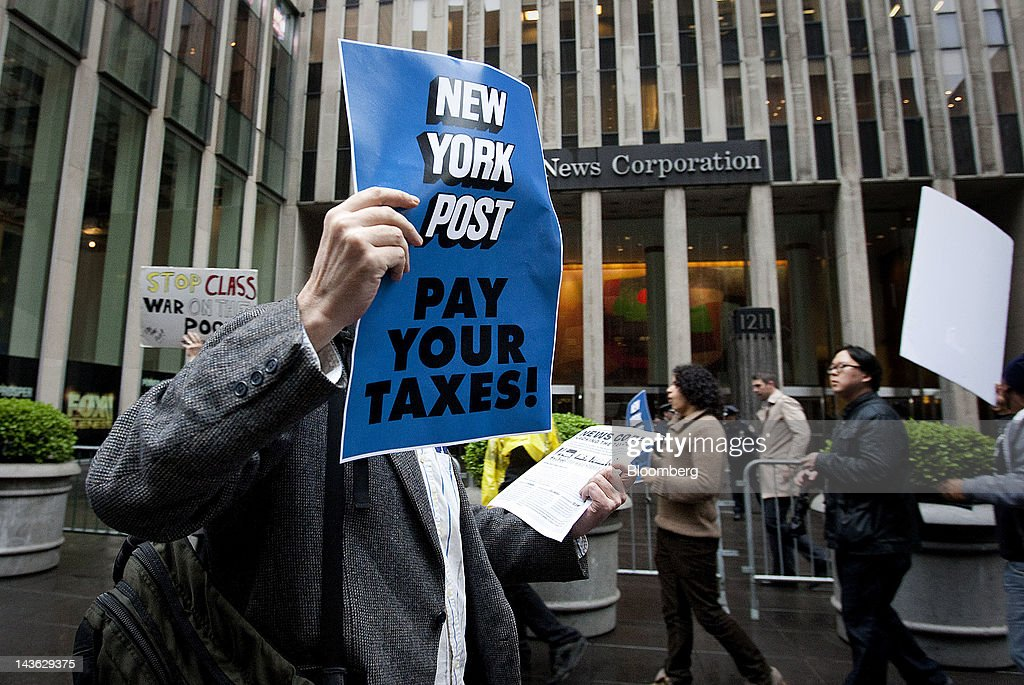 A demonstrator affiliated with the Occupy Wall Street movement holds up a sign in front of News Corp. headquarters in New York, U.S., on Tuesday, May 1, 2012. Occupy Wall Street demonstrators, whose anti-greed message spread worldwide during an eight-week encampment in Lower Manhattan last year, plan marches across the globe today calling attention to what they say are abuses of power and wealth. Photographer: Scott Eells/Bloomberg via Getty Images
