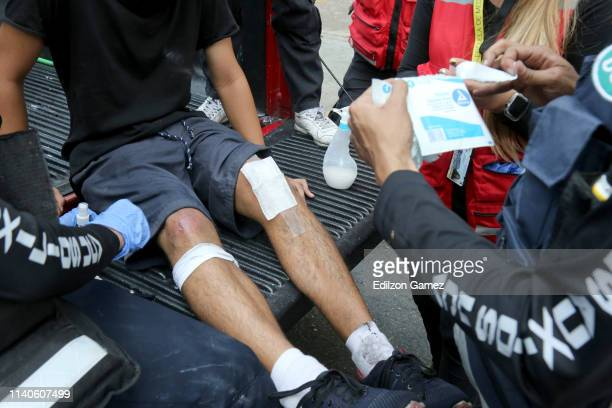 A demonstrator against Nicolás Maduro's government receives medical attention after being injured in a conflict with police forces near Plaza...