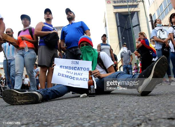 A demonstrator against Nicolás Maduro's government shows a sign that reads 'Without unions there is no democracy' after the May 1 demonstration at...