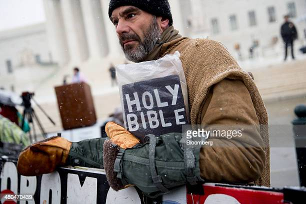 Demonstrator Alan Hoyle holds a bible as he stands outside the US Supreme Court in Washington DC US on Tuesday March 25 2014 Hobby Lobby a...