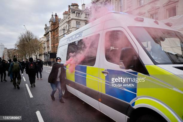 Demonstrator at a 'Kill The Bill' protest against the Government's Police, Crime, Sentencing and Courts Bill holds a smoke flare near the windows of...