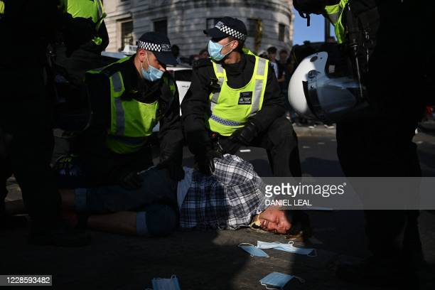TOPSHOT A demonstrator at an antivax rally protest against vaccination and government restrictions designed to control or mitigate the spread of the...