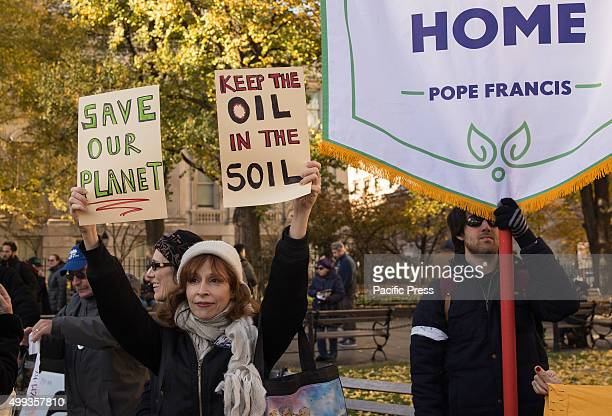 A demonstrator at the Climate March holds aloft signs On the eve of the Paris Climate Summit environmental advocates rallied near New York City's...