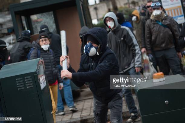 A demonstrator attacks a pay station on November 16 in Nantes western France on the sidelines of a demonstration marking the first anniversary of the...