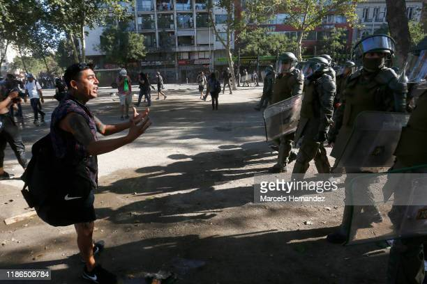 Demonstrator attempts to talk to riot police officers during protests against president Piñera at Plaza Italia on December 4, 2019 in Santiago,...