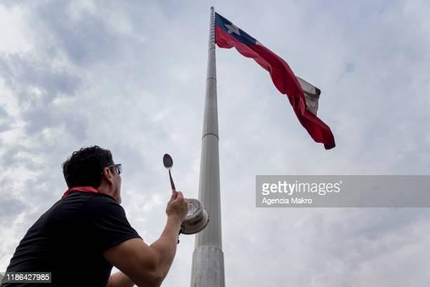 Demonstrator bangs a pot next to the Bicentennial Flag near Palacio de La Moneda during a protest against the government of president Sebastian...