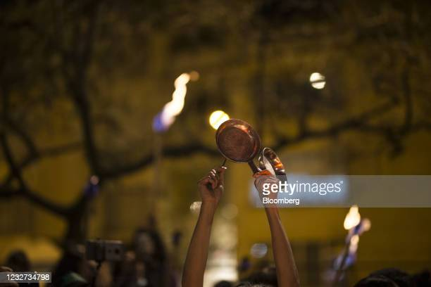 Demonstrator bangs a saucepan as a symbol of protest while attending a vigil for the victims of alleged police violence during protests against the...