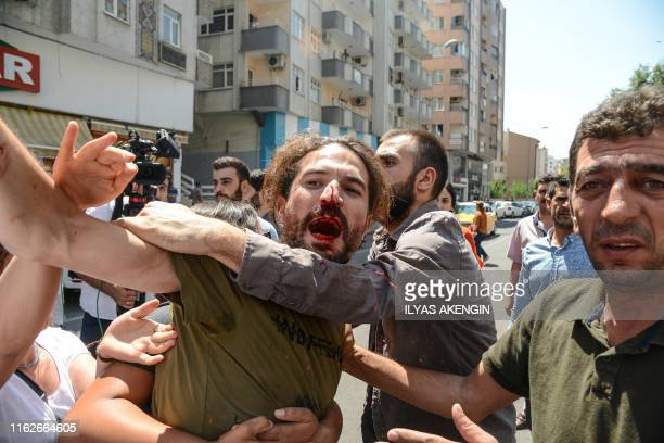 Demonstrator bleeds after getting injured during clashes with riot police during a protest against the replacement of Kurdish mayors with state...
