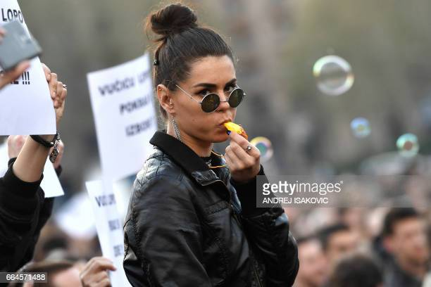 A demonstrator blows a whistle during a protest in front of the National assembly building in Belgrade on April 4 2017 Thousands of mostly young...