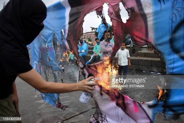 Demonstrator burns a banner with a photograph of Guatemala's Attorney General Consuelo Porras during a protest demanding the resignation of...
