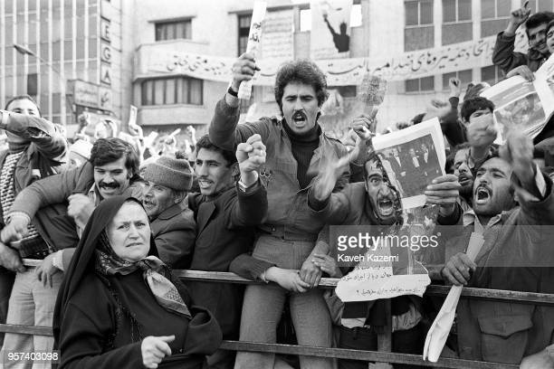Demonstrator burns a photo of the shah while chanting anti shah and US slogans with others outside the American Embassy which is occupied by...