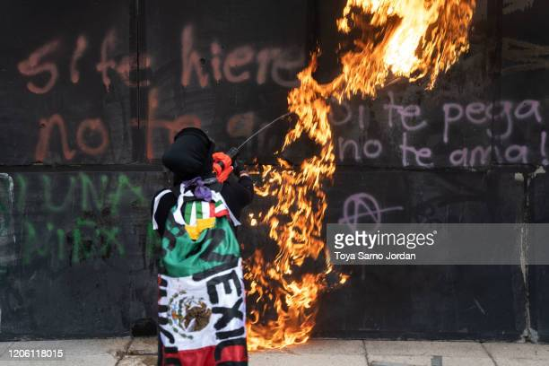 A demonstrator burns a wall during a rally on International Women's Day on March 8 2020 in Mexico City Mexico
