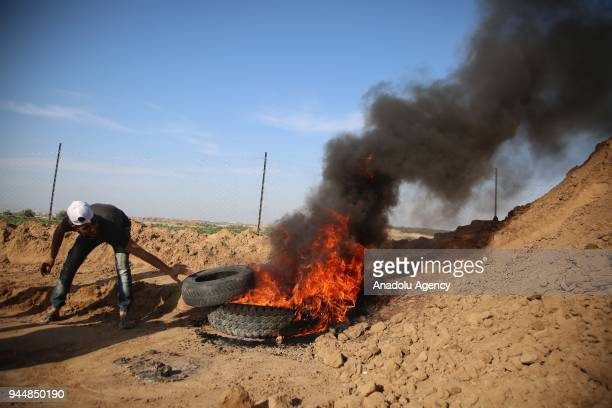 A demonstrator burns tires in response to Israeli soldiers' intervention to remark the 'Great March of Return' at the border east of Al Bureij...