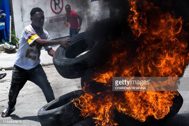 A demonstrator burns tyres during a protest against the ruling government on Haitian Flag Day in PortauPrince May 18 2019 Protesters marched through...