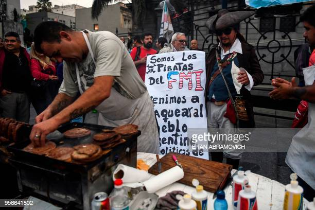 A demonstrator buy a burguer during a protes outside the National Congress while legislators debate a bill to put a stop on public services taxes...