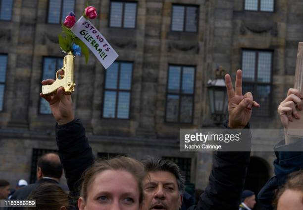 A demonstrator carries a fake gun with roses and a sign saying this is not a war during the demonstration organised today in Amsterdam in support of...