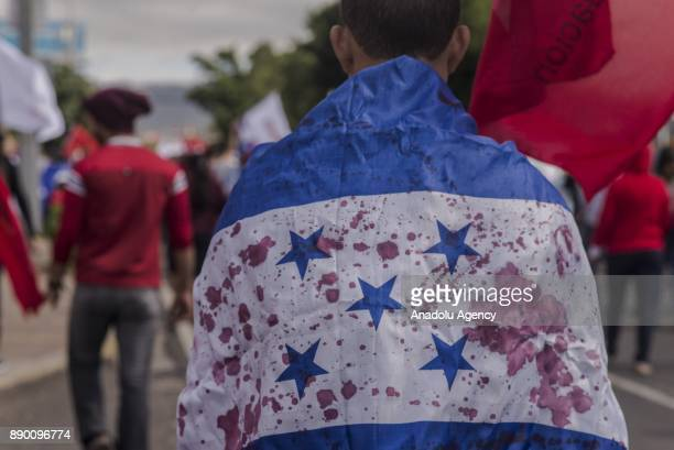 A demonstrator carries a Honduran flag stained with red paint representing the blood of Honduran people due to the political turmoil caused by the...