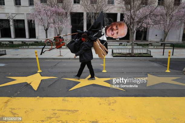 Demonstrator carries a large puppet of President Joe Biden away following a protest by indigenous environmental activists outside the White House...
