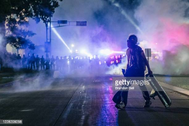 A demonstrator carries a makeshift shield across the street on August 25 2020 in Kenosha Wisconsin As the city declared a state of emergency curfew a...