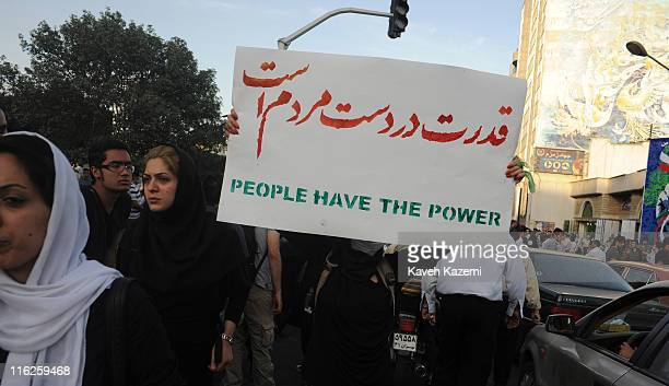 A demonstrator carries a 'People Have The Power' banner during a peaceful march in Vali Asr square Tehran 17th June 2009 Thousands of people took to...