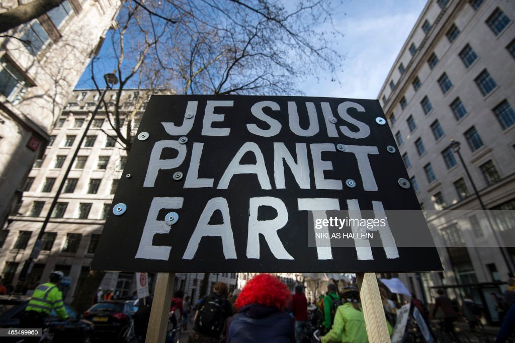 A demonstrator carries a placard reading 'Je suis Planet Earth' (I am Planet Earth) during The People's Climate march in central London on March 7, 2015. Around 5,000 protesters marched on the British parliament Saturday demanding greater action on climate change, exactly two months ahead of the general election. The march was led by a man with green leaves attached to his head, who was riding a bicycle with large wings bearing the slogan: 'Look after your mum.' AFP PHOTO / NIKLAS HALLE'N
