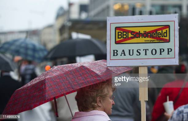 "Demonstrator carries a placard reading ""stop construction"" during a protest against Berlin's new Schoenefeld airport, the Berlin Brandenburg..."
