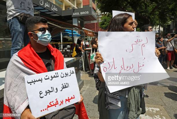 "Demonstrator carries a placard which reads in Arabic "" He did not commit suicide, he was killed in cold blood"" as they gather to denounce the death..."
