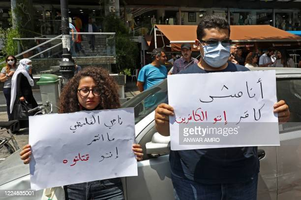 """Demonstrator carries a placard which reads in Arabic """"I am not a sinner, you are the sinners"""" as they gather to denounce the death of a 61-year-old..."""