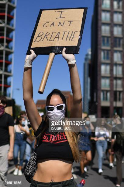 Demonstrator carries a placards as she joins a march in the road near the US Embassy in London on May 31, 2020 to protest the death of George Floyd,...