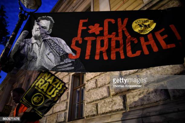 A demonstrator carries a sign reading 'Nazis get out' under a sign reading 'Fuck Strache' during a protest on October 13 2017 in Vienna Austria...