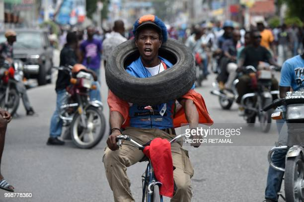 TOPSHOT A demonstrator carries a tire during a march through the streets of PortauPrince on July 14 2018 to protest against the government of...