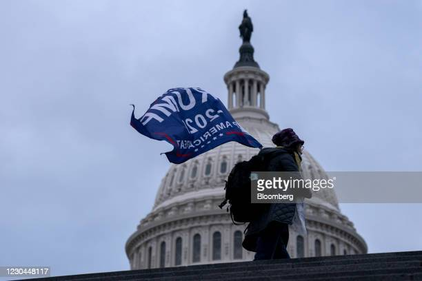 """Demonstrator carries a """"Trump 2020"""" flag outside the U.S. Capitol in Washington, D.C., U.S., on Wednesday, Jan. 6, 2021. The House and Senate will..."""