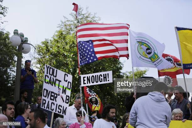 A demonstrator carries an upside down American flag during an antiracism rally in front of the US Embassy in Ottawa Ontario Canada on Aug 23 2017 The...