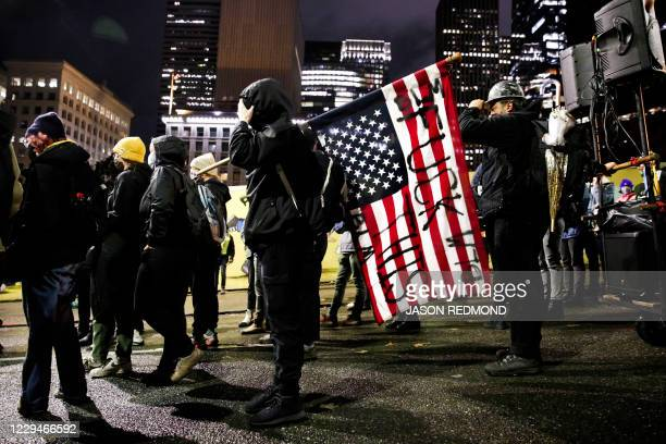 """Demonstrator carries an upside down US flag during a march to """"Count Every Vote, Protect Every Person"""" on the day after the US Presidential Election..."""