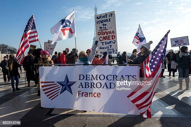 A demonstrator carries signs and american flags during a rally in solidarity with supporters of the Women's March in Washington and many other cities...