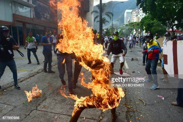 TOPSHOT A demonstrator catches fire after the gas tank of a police motorbike exploded during clashes in a protest against Venezuelan President...