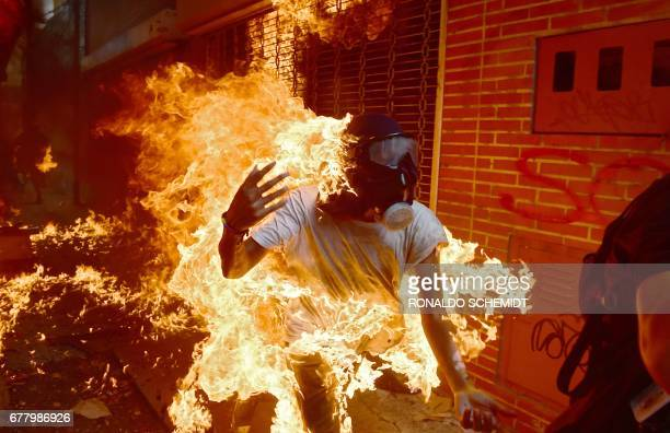 TOPSHOT A demonstrator catches fire during clashes with riot police within a protest against Venezuelan President Nicolas Maduro in Caracas on May 3...
