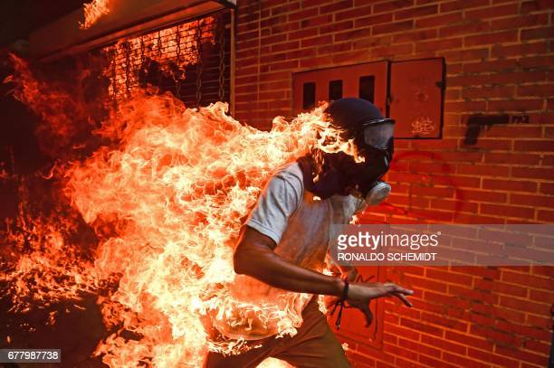 A demonstrator catches fire during clashes with riot police within a protest against Venezuelan President Nicolas Maduro in Caracas on May 3 2017...