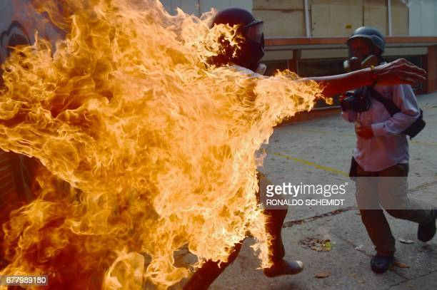 Demonstrator catches fire during clashes with riot police within a protest against Venezuelan President Nicolas Maduro, in Caracas on May 3, 2017....