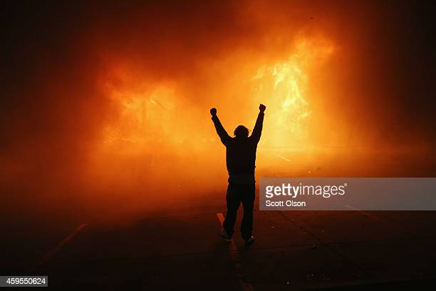 Demonstrator celebrates as a business burns after it was set on fire during rioting following the grand jury announcement in the Michael Brown case...