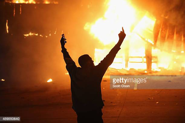 A demonstrator celebrates as a business burns after it was set on fire during rioting following the grand jury announcement in the Michael Brown case...