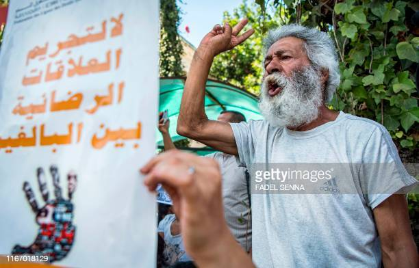 A demonstrator chants slogans as another holds up a sign reading Arabic no to the criminalisation of consensual relations between adults during a...