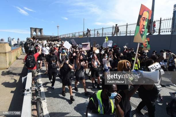 A demonstrator chants using a megaphone while crossing the Brooklyn Bridge during a protest on Juneteenth on June 19 2020 in the Brooklyn borough of...