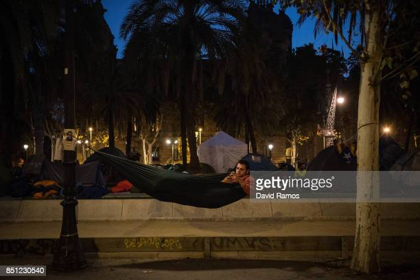 A demonstrator checks his mobile phone as he lies on a hammock after spending the night in front of the Catalan High Court building on September 22...