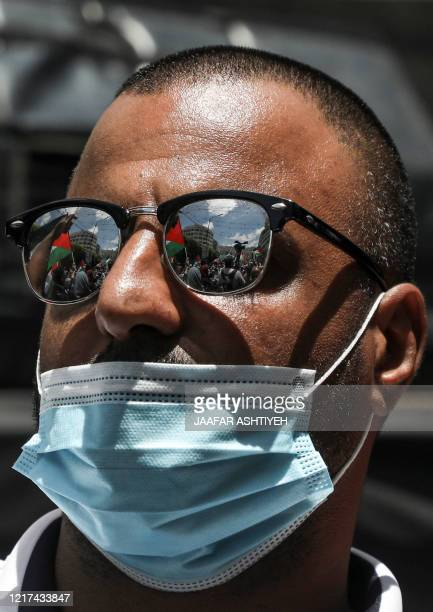 Demonstrator clad in sunglasses and mask looks on during a protest against Israeli plans to annex parts of the occupied West Bank, in the West Bank...