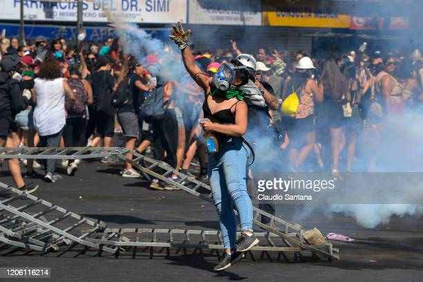 Demonstrator clash with riot police during protests as part of the International Women's Day on March 8 2020 in Santiago Chile