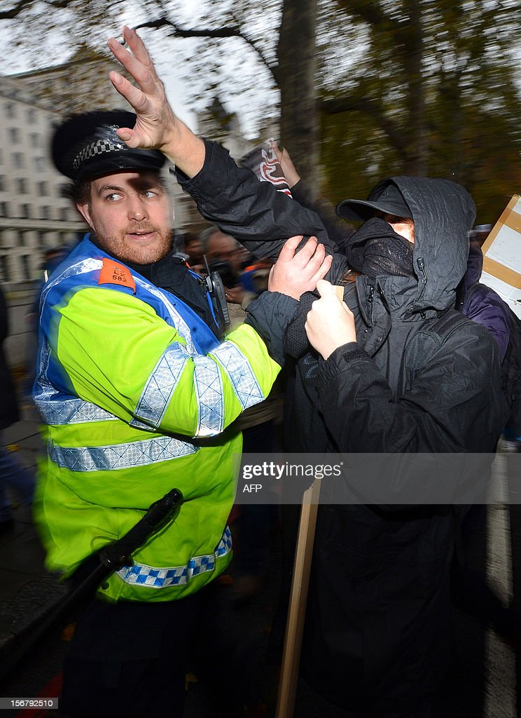 A demonstrator clashes with a police officer during a student rally in central London on November 21, 2012 against sharp rises in university tuition fees, funding cuts and high youth unemployment.