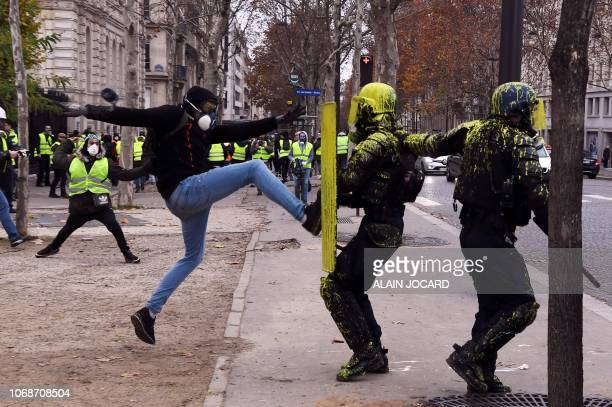 Demonstrator clashes with riot police during a protest of Yellow Vests against rising oil prices and living costs on the Champs Elysees in Paris, on...