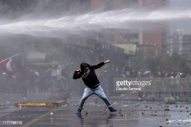 A demonstrator clashes with riot police during the sixth day of protests against President Sebastian Piñera on October 23 2019 in Santiago Chile...